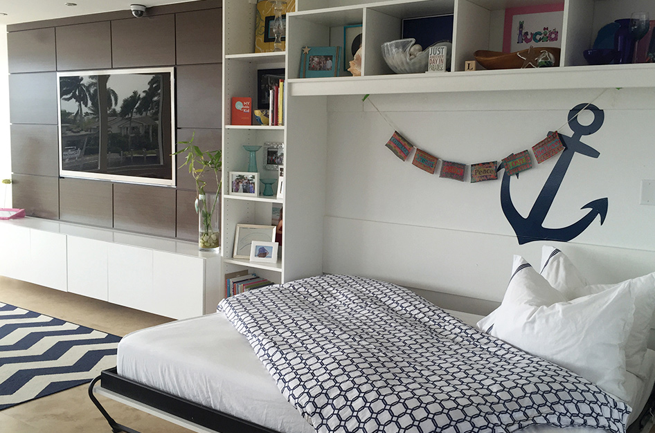 Pulled out Murphy bed with open shelves above and to the side.