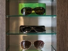 Trinh Vo Yezter Commercial Client Story Close Up of Glass Sunglass Shelving with Dark Brown Finish