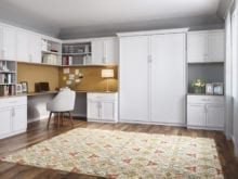 Office Space with White Shelving Cabinets Built in Desk and Murphy Bed with Deep Yellow Accents