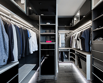 Detailed shot of walk in closet with accent lighting on the floor and dark wood finish