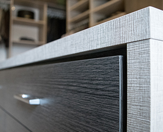 Close up shot of dark gray and brown cabinet with stainless steel hardware