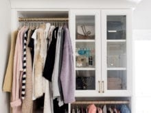Hanging clothing space and glass cabinet doors in fashion blogger Brittany Sjogren's walk in closet by California Closets