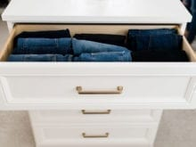 White drawers with gold handles fashion blogger Brittany Sjogren's walk in closet by California Closets
