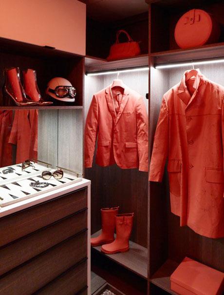 Orange suit jackets hanging by LED lit hanging rods