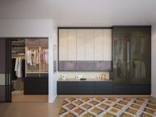 Floor to ceiling wardrobe with pack painted glass next to a custom walk in closet