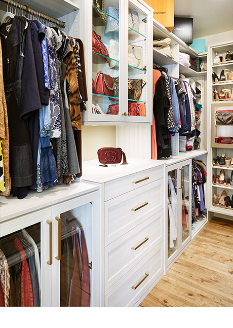 Custom cabinetry for purses and other accessories in custom walk in closet