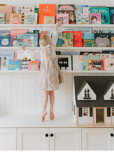 Daughter of photographer Syndey Gerten reaching for book in her new custom playroom storage