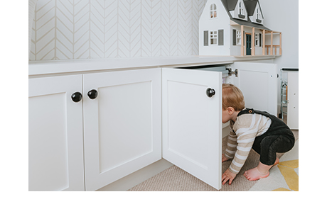 Son of photographer Syndey Gerten peaking inside cabinet of new custom playroom cabinet