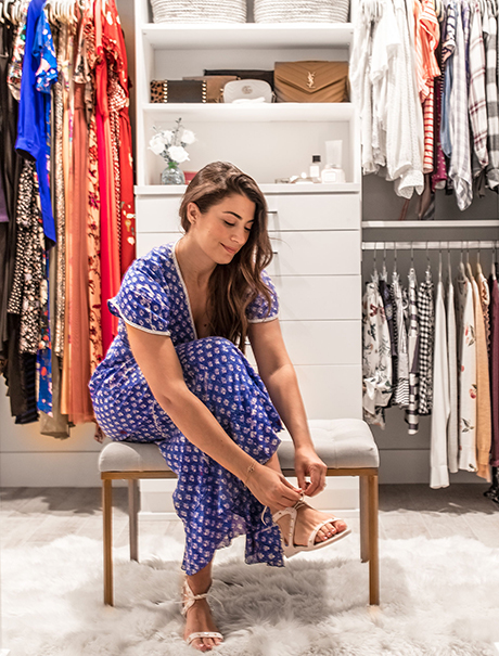 Blogger Lindsay Surowitz sitting in her optimized walk in closet by California Closets
