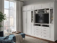 Grey apartment media room with California Closets' wall bed hidden in grey cabinet