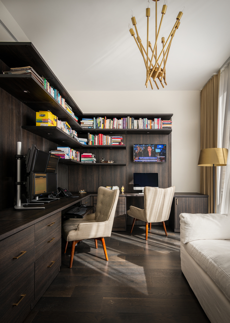 Dark wooden home office with two white chairs and 6 monitor display and book shelf