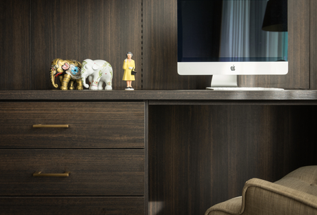 Dark wood home office desk with Apple computer and figurines