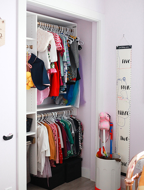White California Closets child's closet with two rows of hanging clothing in pink room