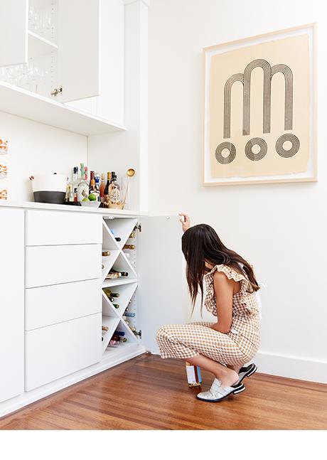 Magazine Editor Angela Tafoya peeking inside her custom dining room cabinets