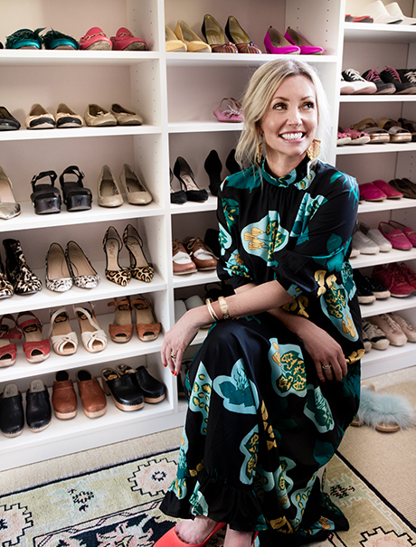 Hannah Crowell smiling and sitting in front of her shoe shelving insider her walk-in closet