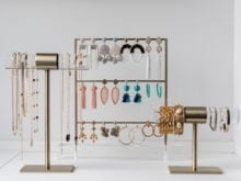 Three jewelry holders covered in earrings, and bracelets