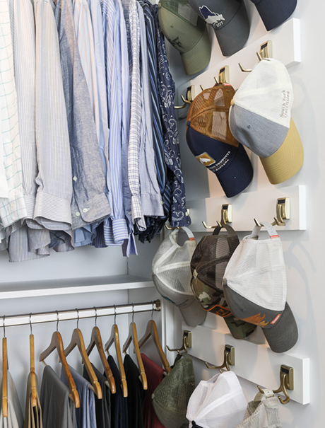 wall hooks with hanging hats next to dress shirts in Kristen Lawler's custom closet